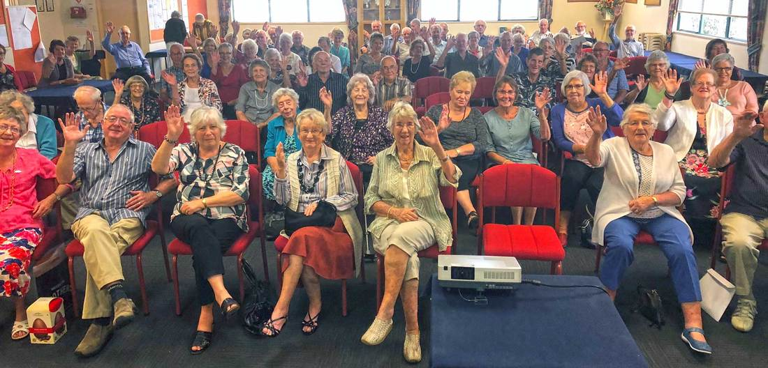 Palmerston North Probus club members group shot of them waving to the camera